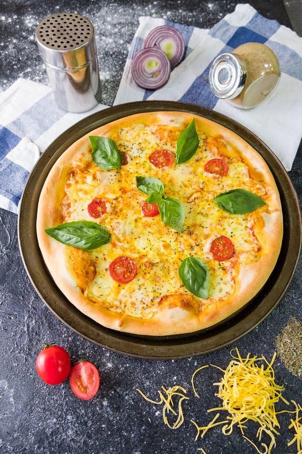 Vlak leg met traditionele Italiaanse pizza met tomaten, basilicum, mozarella op donkere steenlijst en diverse ingrediënten royalty-vrije stock foto's