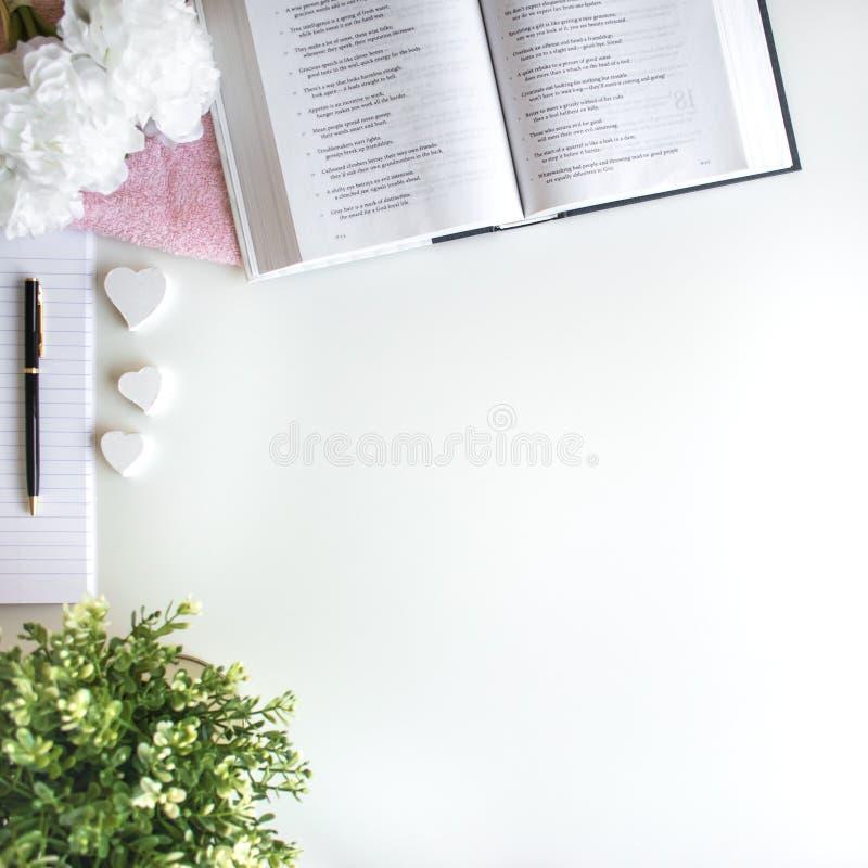 vlak leg met verschillende toebehoren; bloei boeket, roze rozen, open boek, Bijbel stock afbeeldingen
