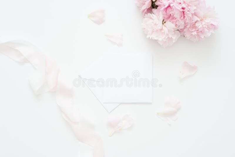 Vlak leg, Minimale vrouwen` s Desktop met blanco pagina omhoog spot, envelop, pioenbloem met bleke bloemblaadjes, - roze zijdelin stock foto's