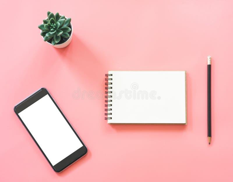 Vlak leg modelontwerp van werkruimtebureau met leeg notitieboekje, smartphone, koffie, kantoorbehoeften op roze pastelkleur met e stock foto's