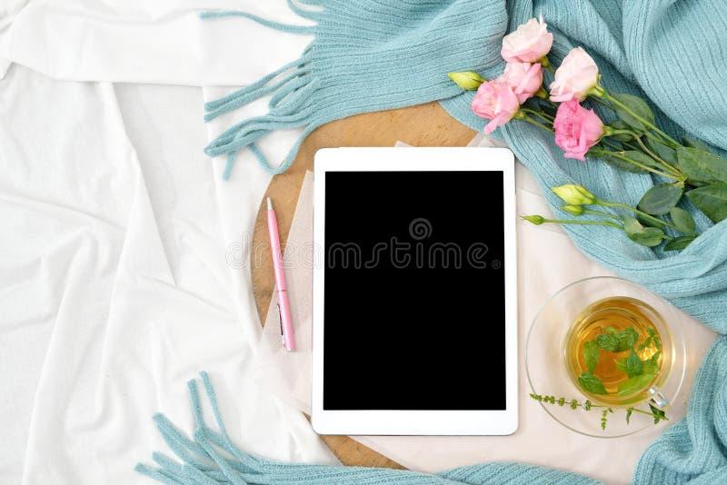 Vlak leg ontbijt in bed met frambozenkaastaart, muntthee en open notaboek, tablet stock fotografie