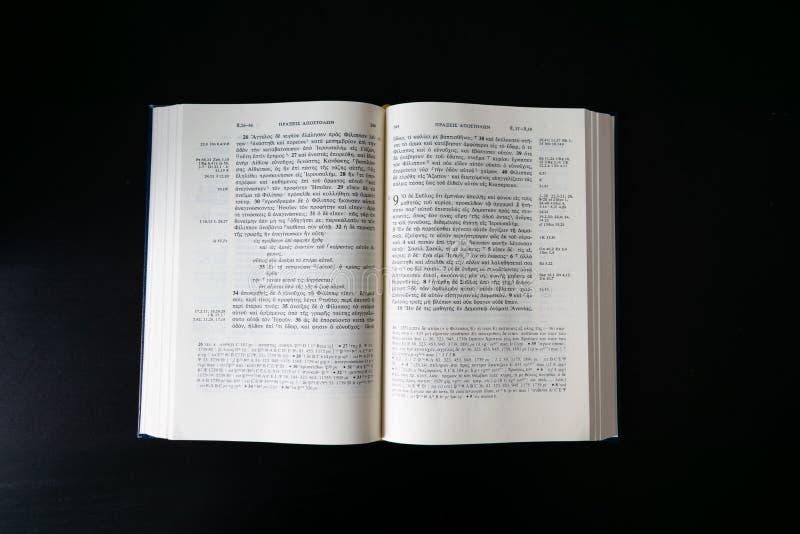 Vlak leg open Bijbel, Grieks Nieuw Testament Novum Testamentum Graece Op zwarte achtergrond stock foto's