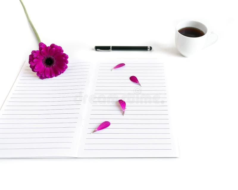 Vlak leg: open dagboek, pagina's, zwarte pen, zwarte thee en roze, purper, violette, rode Gerbera-bloem met bloemblaadjes stock afbeeldingen