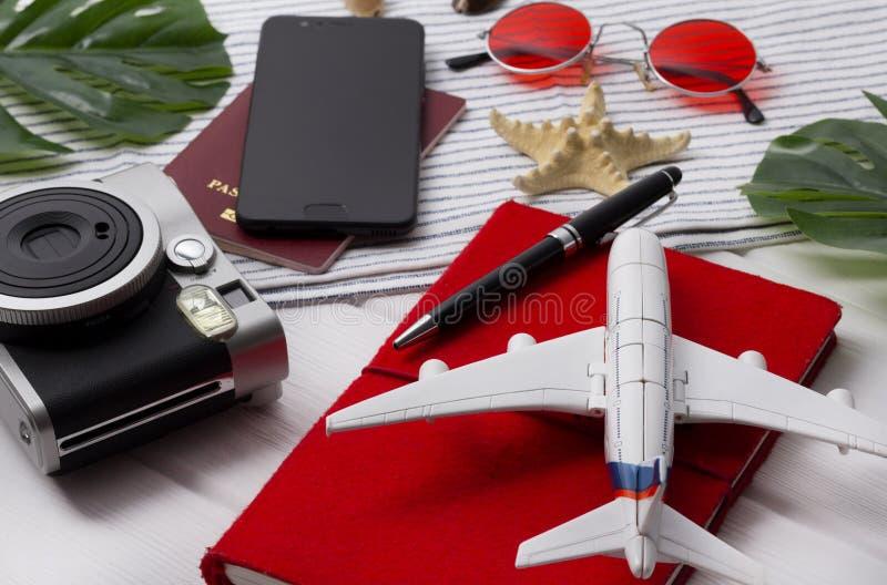 Vlak leg reisconcept: de ontwerper, het paspoort, smartphone, de camera, de pen, de stervis en monstera gaan op houten achtergron stock foto's