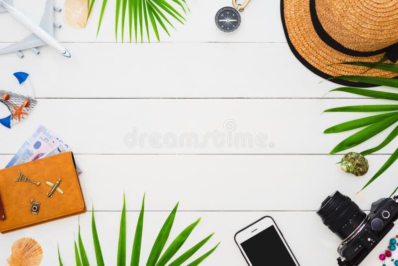 Vlak leg reizigerstoebehoren op witte houten achtergrond met smartphone, palmblad, zeeschelp, camera en toebehoren Jonge volwasse stock foto's