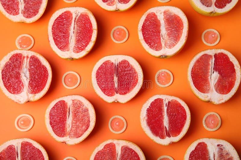 Vlak leg samenstelling met condooms en grapefruits op oranje achtergrond royalty-vrije stock foto