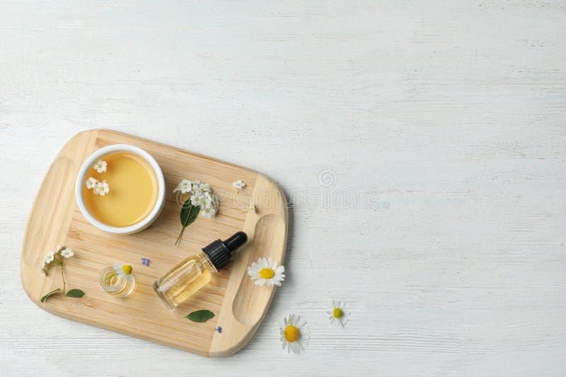 Vlak leg samenstelling met etherische olie en bloemen op witte houten lijst royalty-vrije stock foto