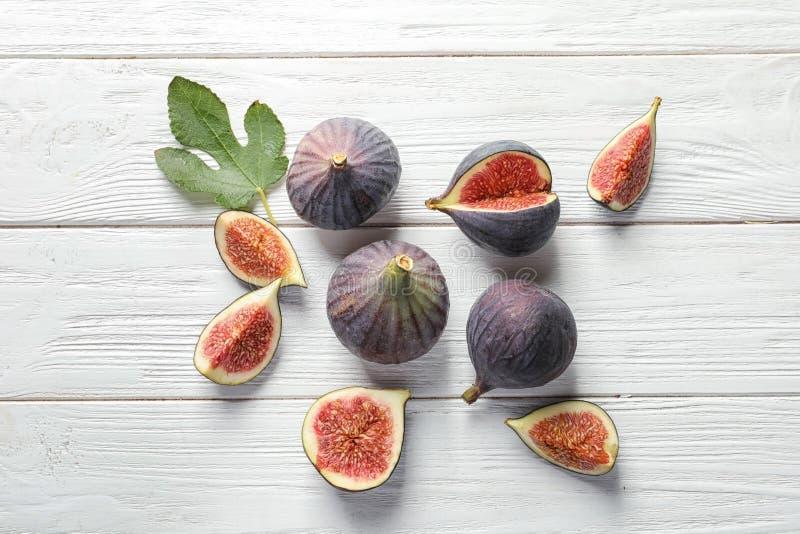 Vlak leg samenstelling met geheel en snijd purpere fig. stock foto