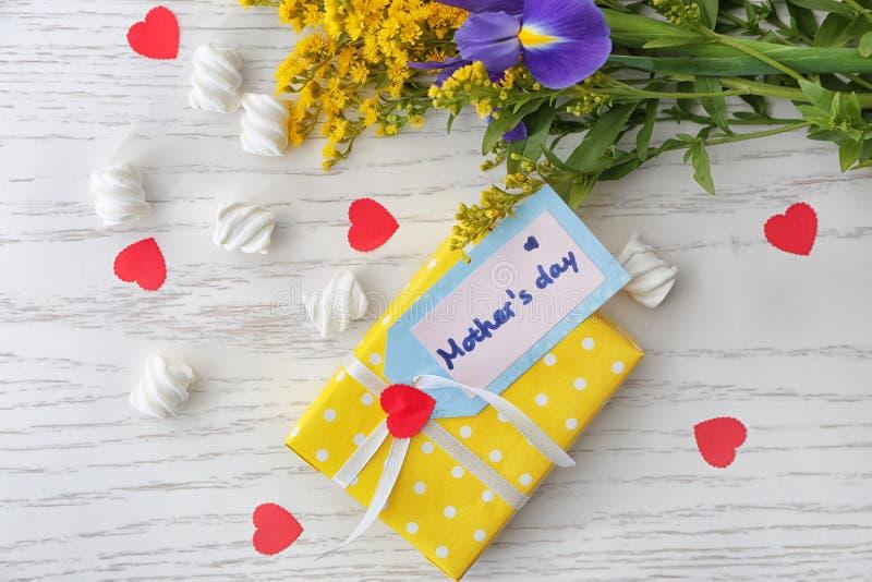 Vlak leg samenstelling met giftvakje, heemst en bloemen op lijst De viering van de moeder\ 's dag stock afbeelding