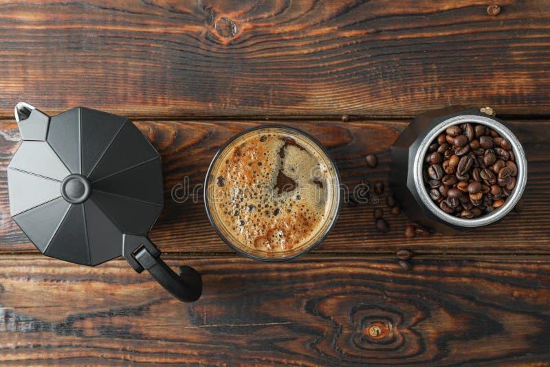 Vlak leg samenstelling met glas verse koffie, koffiezetapparaat en koffiebonen op houten lijst royalty-vrije stock afbeeldingen