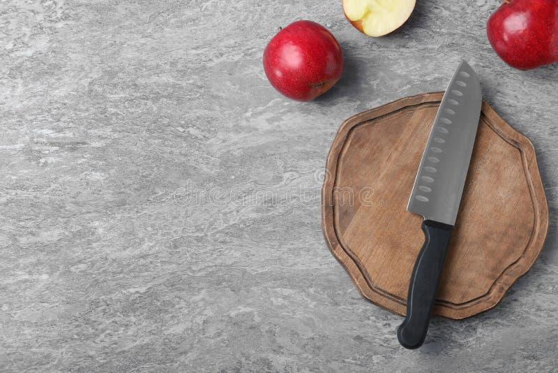 Vlak leg samenstelling met het mes en de appelen van de chef-kok op grijze achtergrond stock foto
