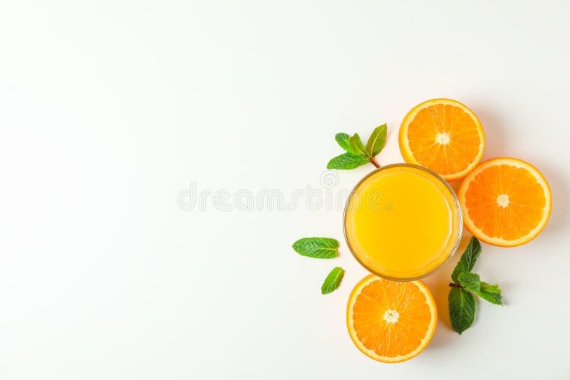 Vlak leg samenstelling met jus d'orange, sinaasappelen en munt op witte achtergrond, ruimte voor tekst royalty-vrije stock foto