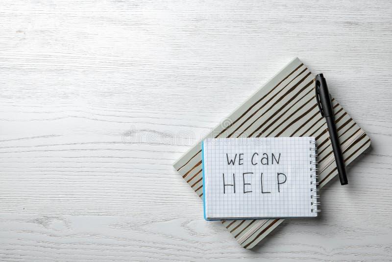 Vlak leg samenstelling met kantoorbehoeften, uitdrukking WIJ KUNNEN HELPEN en ruimte voor tekst royalty-vrije stock afbeeldingen