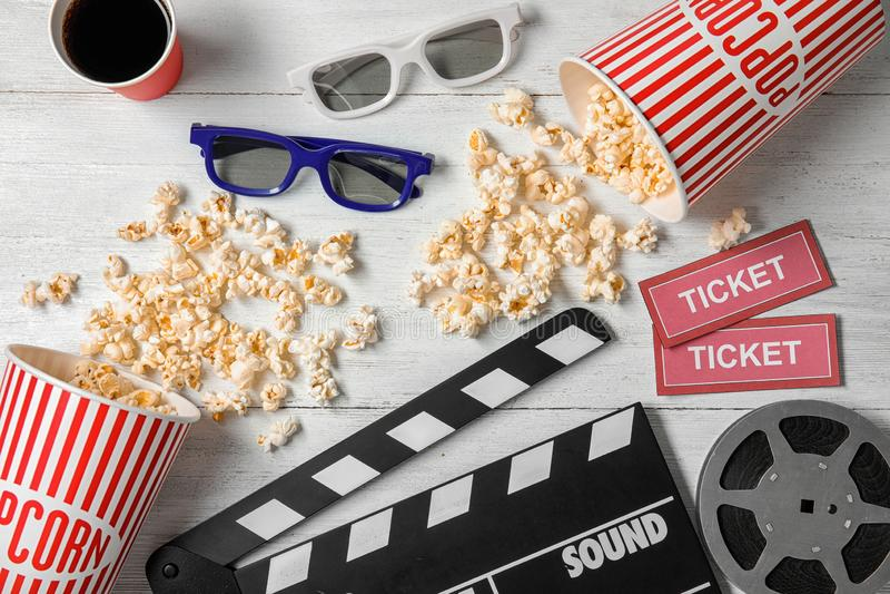 Vlak leg samenstelling met klep, popcorn en kaartjes op houten achtergrond stock foto's