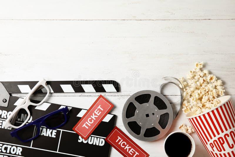Vlak leg samenstelling met klep, popcorn op houten achtergrond Bioskoopsnack stock foto