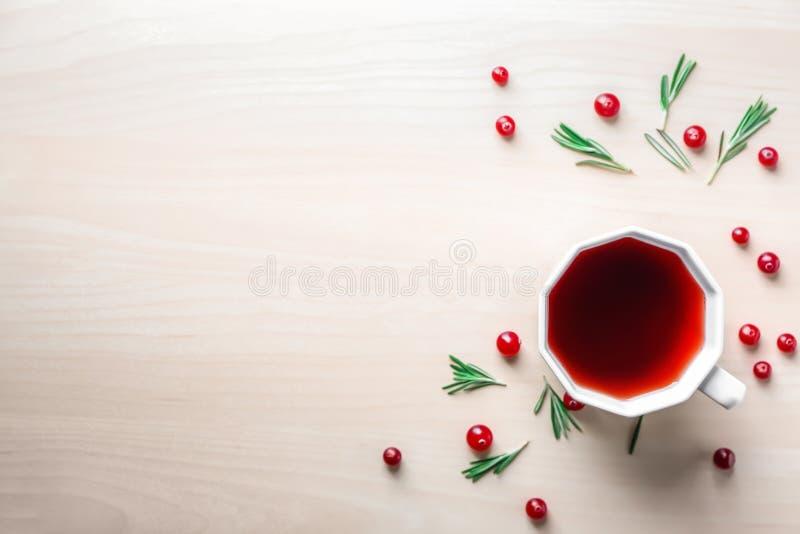 Vlak leg samenstelling met kop rode thee en Amerikaanse veenbessen op lichte achtergrond stock afbeeldingen