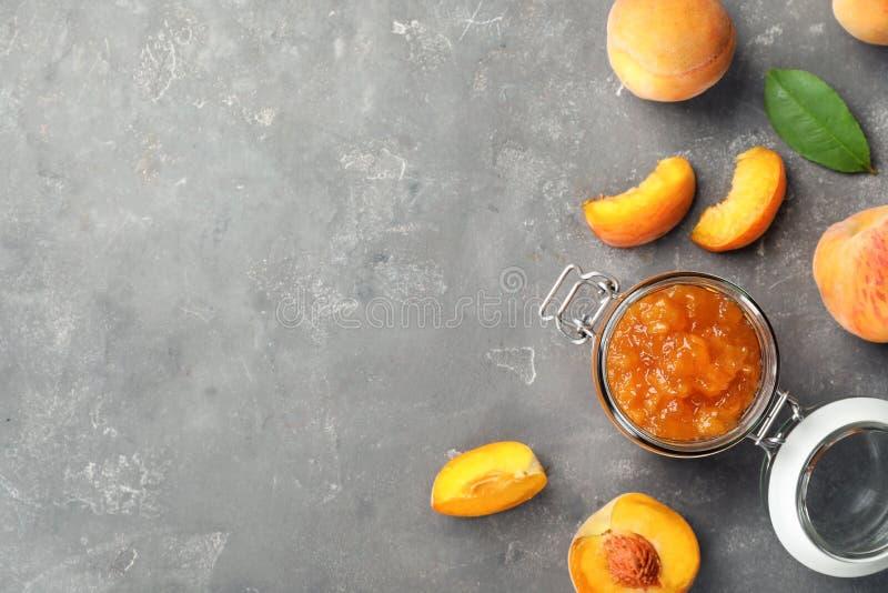 Vlak leg samenstelling met kruik smakelijke perzikjam en vers fruit stock foto's
