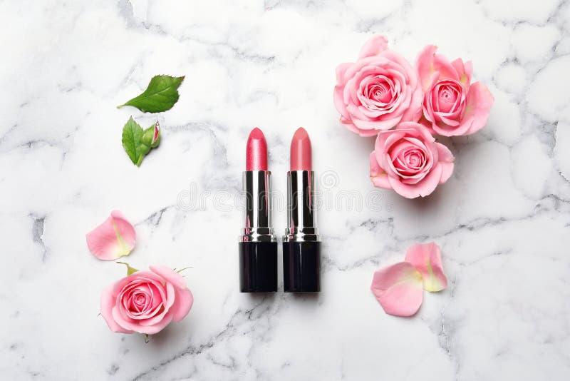 Vlak leg samenstelling met lippenstiften en rozen royalty-vrije stock afbeeldingen