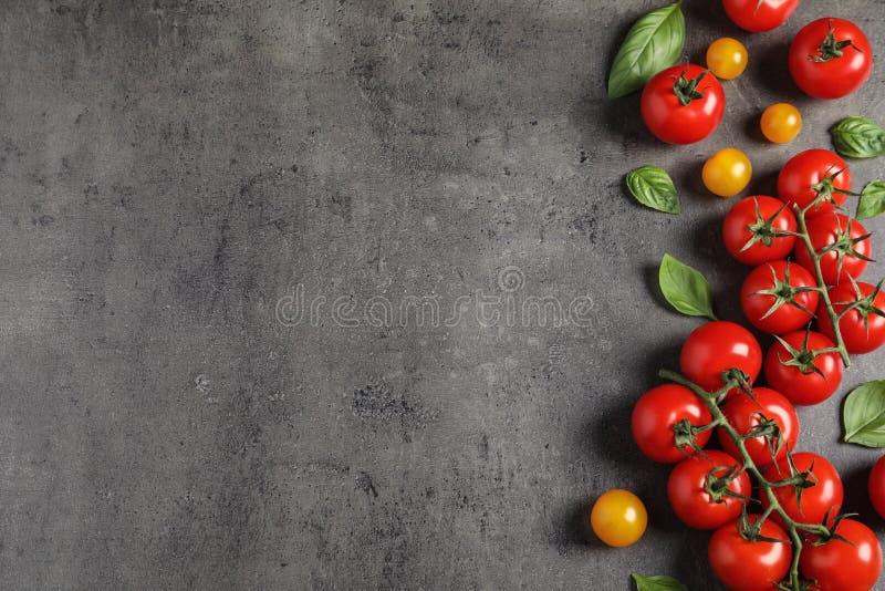 Vlak leg samenstelling met rijpe kersentomaten en basilicumbladeren op kleurenachtergrond royalty-vrije stock foto