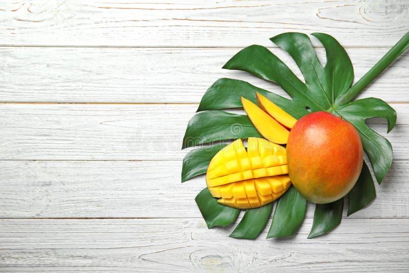 Vlak leg samenstelling met rijpe mango's, monsterablad en ruimte voor tekst royalty-vrije stock afbeeldingen