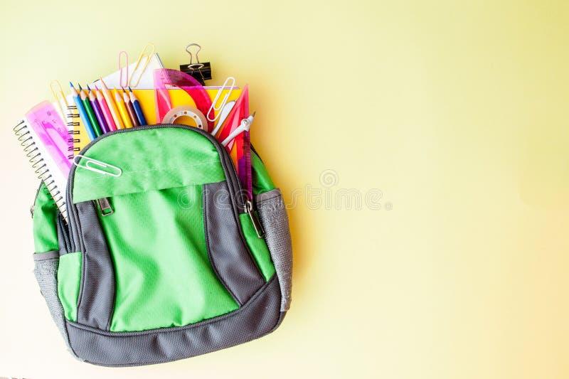 Vlak leg samenstelling met rugzak en schoolkantoorbehoeften op gele achtergrond stock afbeeldingen