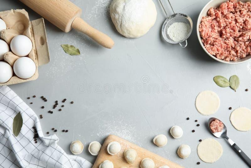 Vlak leg samenstelling met ruwe bollen en ingredi?nten op grijze achtergrond, ruimte voor tekst proces stock afbeeldingen
