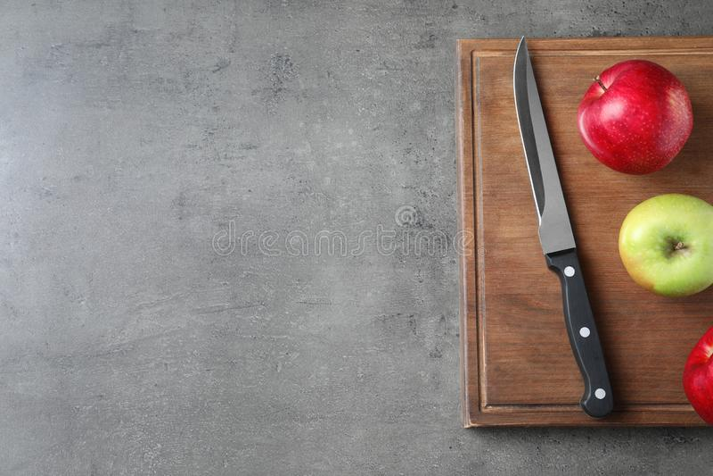 Vlak leg samenstelling met scherp mes, appelen en houten raad op grijze achtergrond stock afbeeldingen