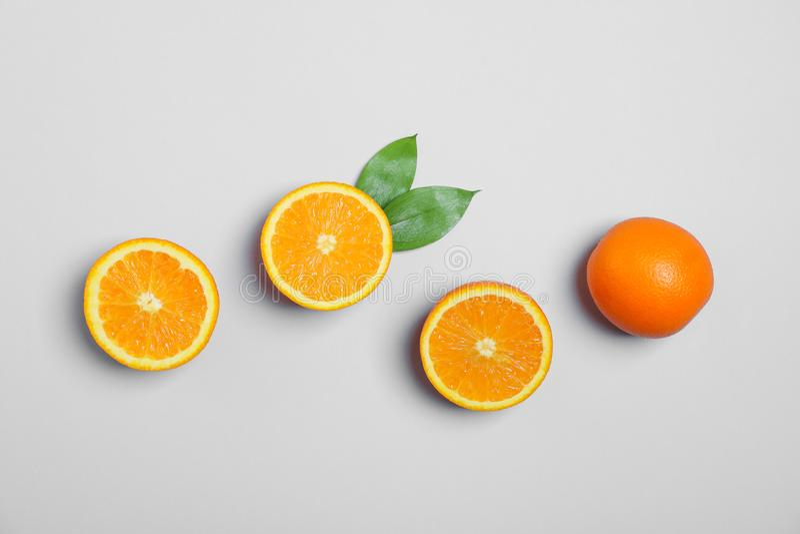 Vlak leg samenstelling met sinaasappelen en bladeren op lichtgrijze achtergrond stock foto