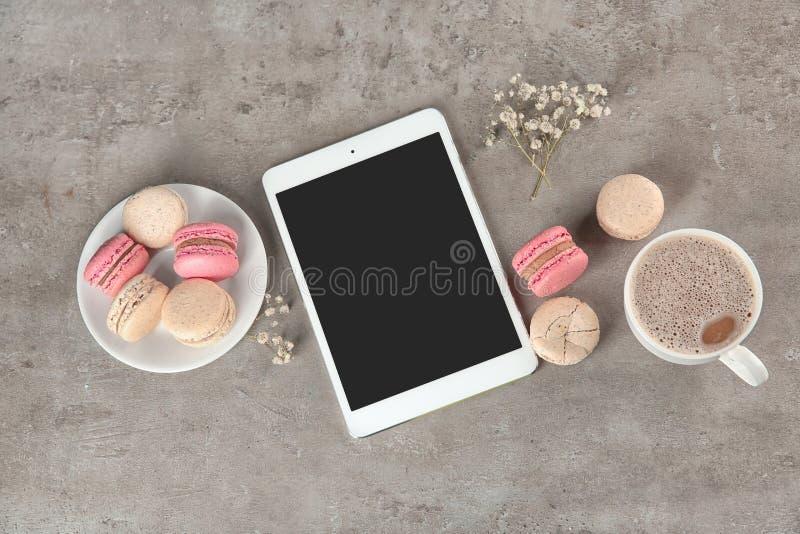Vlak leg samenstelling met smakelijke macarons, kop van koffie en tabletcomputer op grijze achtergrond royalty-vrije stock foto's