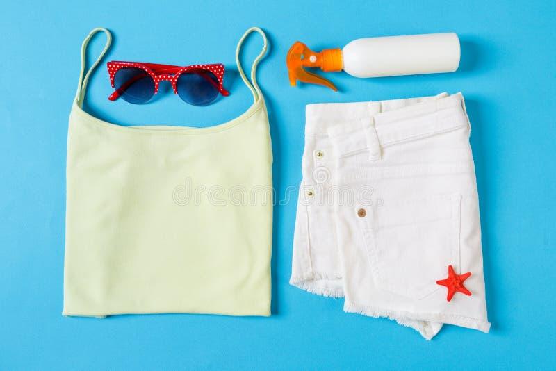 Vlak leg samenstelling met Strandtoebehoren op blauwe kleurenachtergrond De vakantieachtergrond van de zomer Vakantie en reispunt stock afbeelding