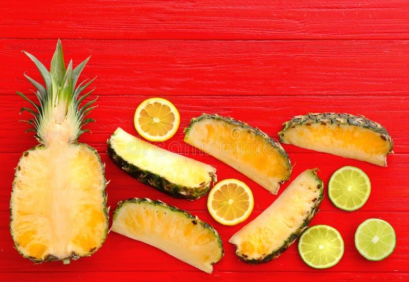 Vlak leg samenstelling met verse gesneden ananas, kalk en citroen op kleuren houten achtergrond royalty-vrije stock afbeelding