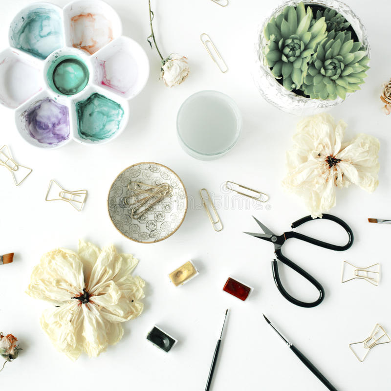 Vlak leg samenstelling met vlinderdasklemmen, schaar, droge tulp, rozen, palet, succulent op witte achtergrond stock afbeelding
