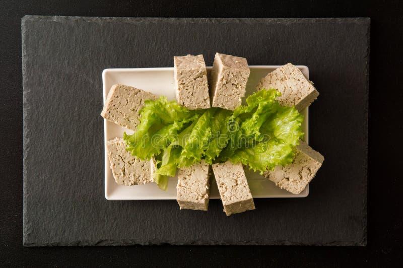 Vlak leg Sluit omhoog Japans voedsel Een gedeeltestukken van tofu, een protein-rich sojakaas, op een witte rechthoekige plaat royalty-vrije stock fotografie