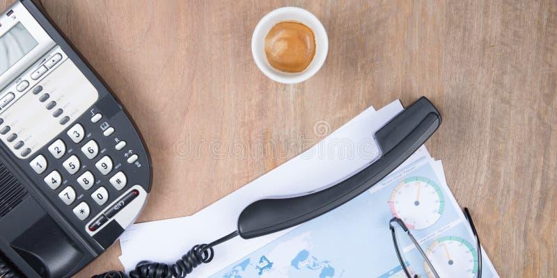 Vlak leg telefoon op het bureau naast een cafékoffie en een statistisch document omhoog wordt vastgehaakt dat royalty-vrije stock fotografie