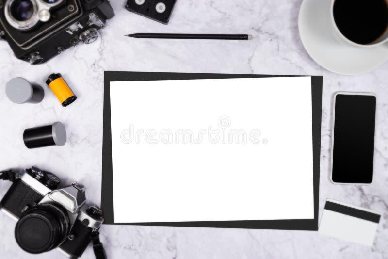 Vlak leg uitstekende camera op witte marmeren achtergrond met wit leeg document en fotografiehulpmiddel stock foto's