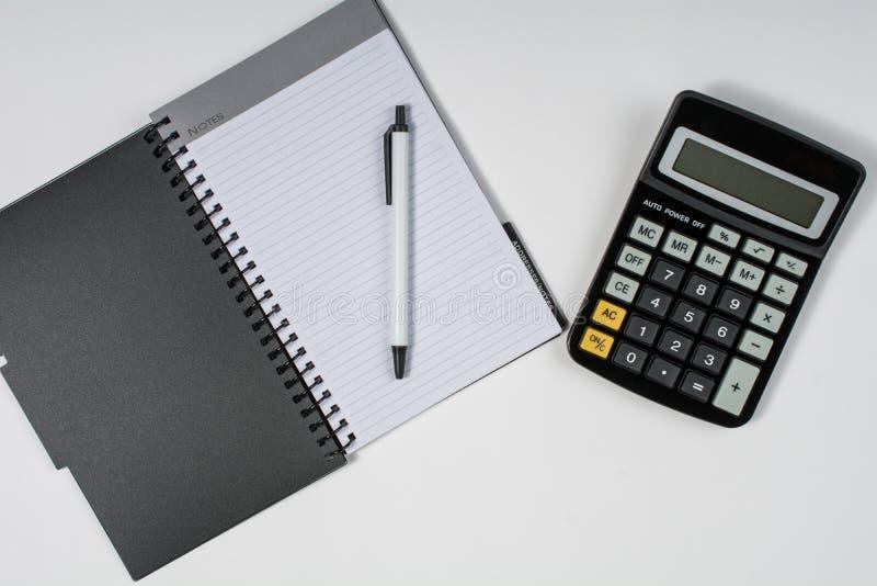 Vlak leg van calculator en notitieboekje met een pen op een witte lijst stock afbeelding