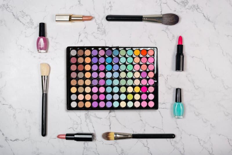 Vlak leg van cosmetischee producten met het kleurrijke palet van de oogschaduwmake-up op marmeren textuur royalty-vrije stock foto's