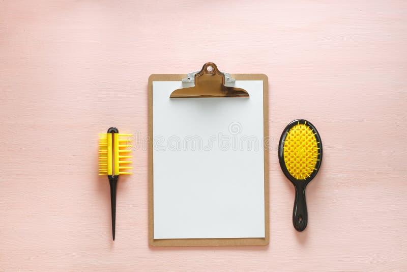 Vlak leg van de kamborstels van de haarkam met handvat voor al types, zakspiegel en de omslagtablet, op roze exemplaar royalty-vrije stock afbeelding