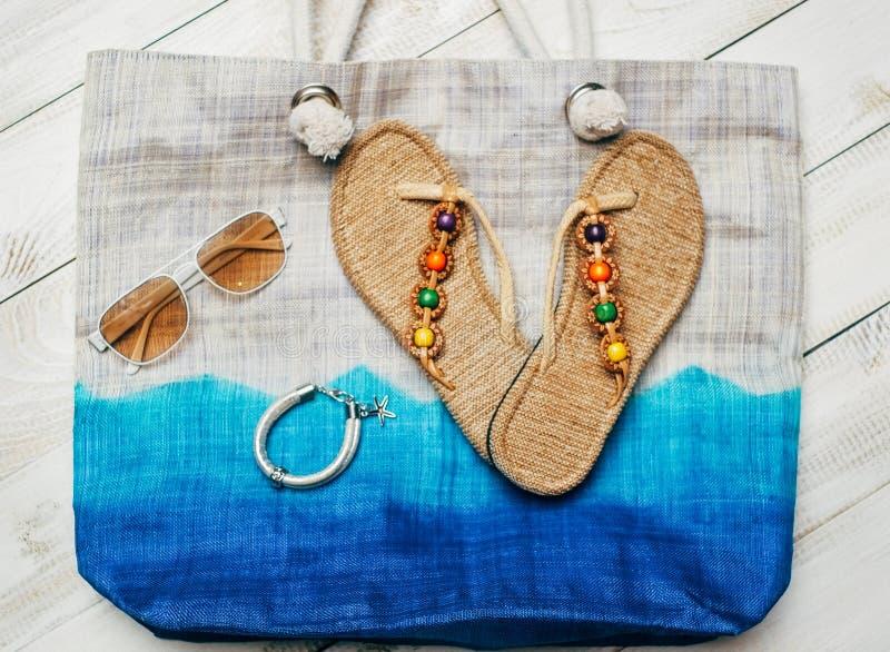 Vlak leg van de zomermanier met pantoffels en zonnebril bovenop de zak op witte houten achtergrond royalty-vrije stock afbeelding