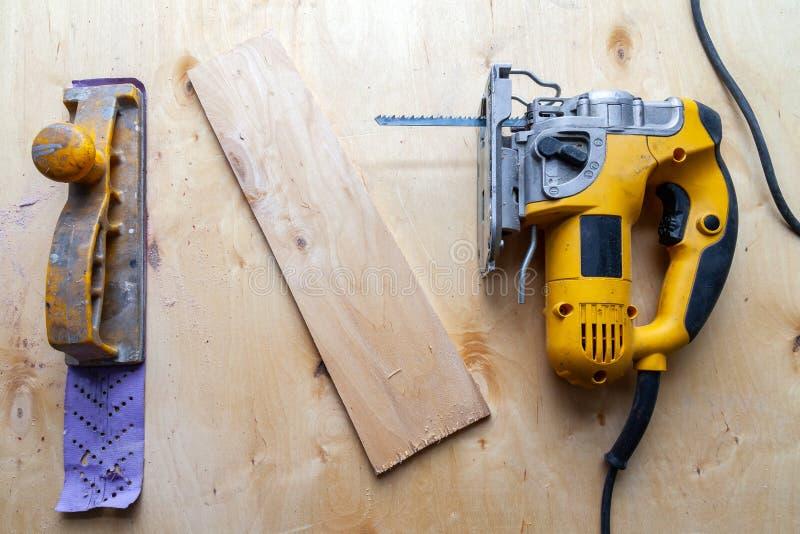 Vlak leg van een geel elektrisch figuurzaag en handvliegtuig klaar voor het werkgebruik op de werkbank met gezaagd triplex in een royalty-vrije stock foto's