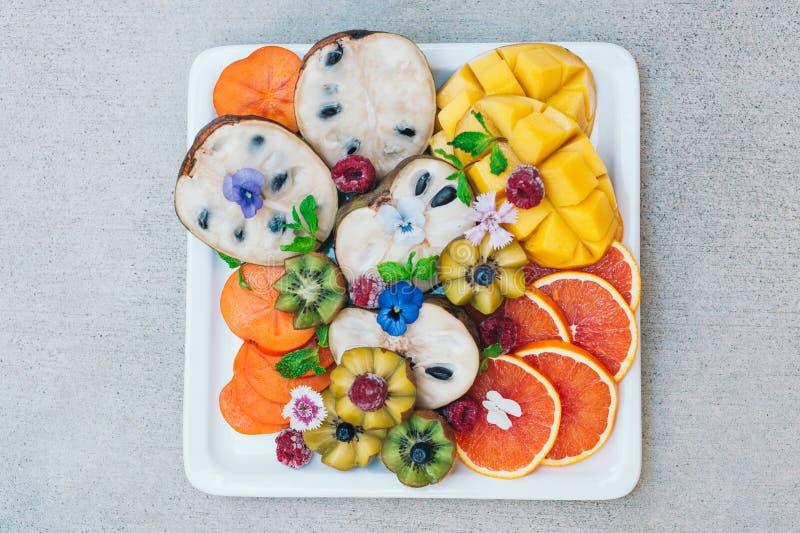 Vlak leg van exotische tropische vruchten Gouden kiwi, persimone, framboos, mango, sinaasappelen en munt Plaat van verse verfraai stock foto's