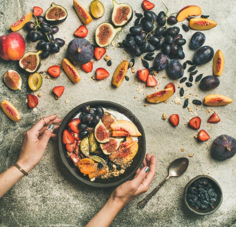 Vlak-leg van Griekse yoghurt, fruit, de kom van chiazaden in handen royalty-vrije stock fotografie