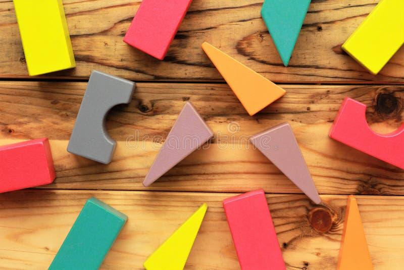 Vlak leg van heldere kleurrijke houten die cijfers op houten lichtbruine planken, abstracte achtergrond worden verspreid stock fotografie
