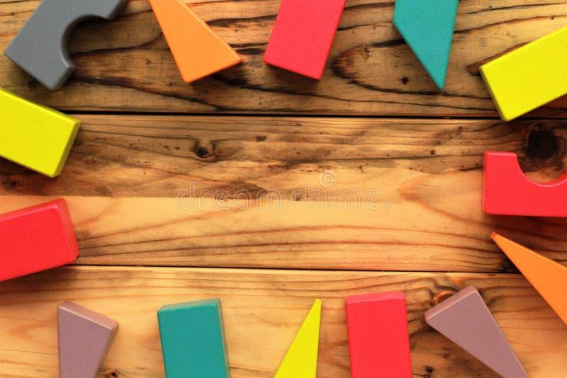 Vlak leg van heldere kleurrijke houten die cijfers op houten lichtbruine planken, abstracte achtergrond worden verspreid stock foto's