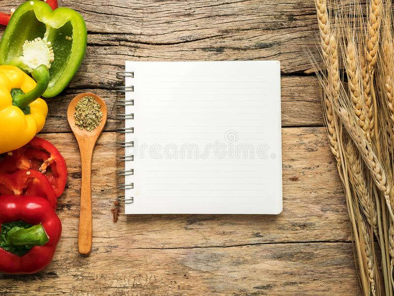 Vlak leg van lege recepten kokende boek en werktuigen met kruiden en kleurrijke groene paprika over houten achtergrond Hoogste me stock afbeeldingen