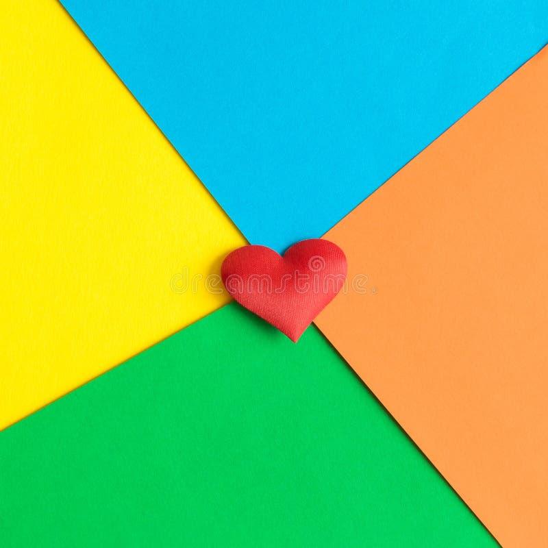 Vlak leg van rood hart op multicolored achtergrond Ruimte voor exemplaar stock foto's