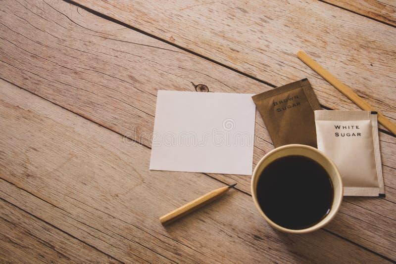 Vlak leg van zwarte koffie in Witboekkop met witte en bruine suikerzakken en houten stok op houten lijst als achtergrond royalty-vrije stock afbeeldingen