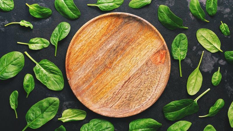 Vlak leg verse bladeren van spinazie en een lege houten plaat op een donkere achtergrond De ruimte van het exemplaar royalty-vrije stock foto's