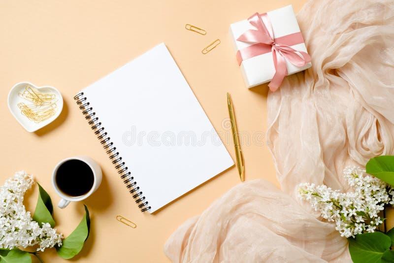 Vlak leg vrouwelijke toebehoren, blocnote, paperclip, gouden pen, giftdoos, koffiekop, witte lilac bloemen op pastelkleuren stock foto