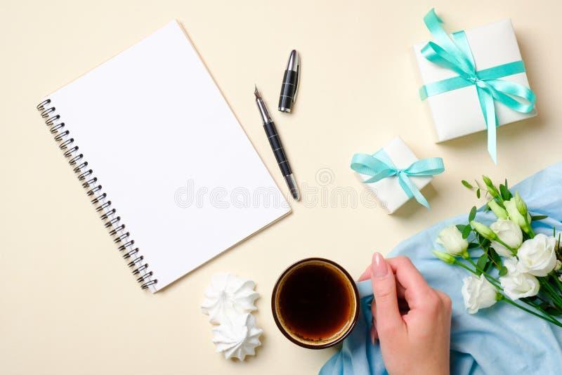 Vlak leg vrouwelijke toebehoren, giftvakje, document blocnote, koffiekop, heemst, witte rozenbloemen op pastelkleurenbeige stock afbeelding